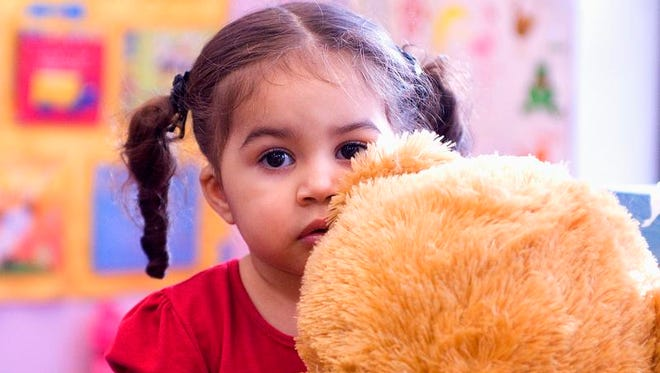 Camila Canales, 2, of Rochester, hugs her new Teddy bear, a gift from the Rochester Latino Rotary Club and the Toys for Tots program on Three Kings Day at the Ibero Early Childhood Services Daycare in this 2011 file photo.