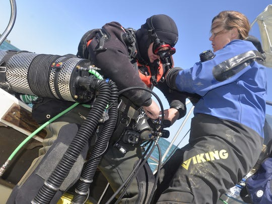 Tamara Thomsen (right) of the Wisconsin Historical Society helps volunteer diver Gayle Orner with her scuba equipment.