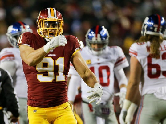 Washington Redskins outside linebacker Ryan Kerrigan (91) celebrates his sack of New York Giants quarterback Eli Manning (10) in the background during the first half of an NFL football game in Landover, Md., Thursday, Nov. 23, 2017. (AP Photo/Mark Tenally)