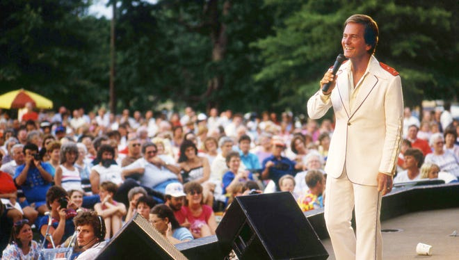 A hometown crowd of 8,000 braves the heat July 13, 1976 to welcome Pat Boone back to the Centennial Park stage where his career was launched in 1952. Boone is singing one of his pop tunes from the Ô50s and Ô60s during a free Homecoming Õ86 concert.
