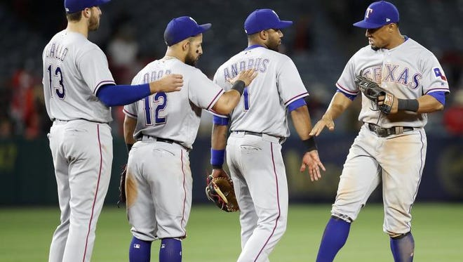Texas Rangers third baseman Joey Gallo, second baseman Rougned Odor, shortstop Elvis Andrus and center fielder Carlos Gomez, from left, celebrate after the Rangers defeated the Los Angeles Angels 8-3 in a baseball game, Wednesday, April 12, 2017, in Anaheim, Calif. (AP Photo/Ryan Kang)
