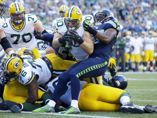 Green Bay Packers fullback John Kuhn (30) dives in for a touchdown against the Seattle Seahawks during a Sept. 4, 2014 game in Seattle. Kuhn earned All-Pro honors this last year, and resigned with Green Bay during the offseason.