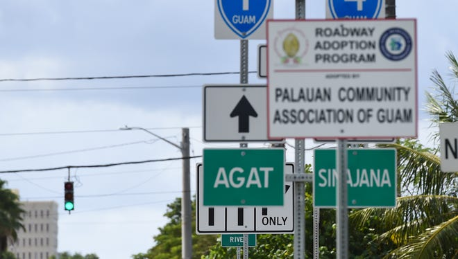 A junction sign for the Paseo Loop intersection is partially obstructed by another road sign and a Palauan Community Association of Guam Roadway Adoption Program sign in Hagåtña on Dec. 14, 2017.