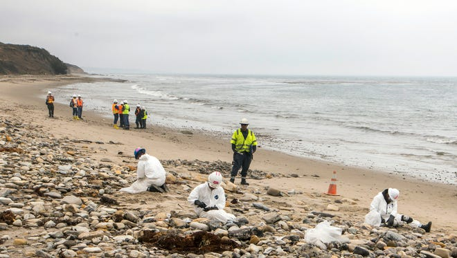 In this June 10, 2015, file photo, Shoreline Cleanup Assessment Technique team members evaluate oil coverage, far left, as workers clean up areas affected by an oil spill at Refugio State Beach, north of Goleta, Calif. Nearly two months after an oil pipeline break fouled beaches near Santa Barbara, California, the costly cleanup is about finished, officials said Thursday, July 16, 2015.