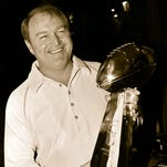 ** FILE ** This is a Jan. 19, 1979 file photo showing Pittsburgh Steelers coach Chuck Noll holding the Vince Lombardi trophy during a pre-Super Bowl news conference in Miami. Planners may name a street to be built near the Pittsburgh Steelers' stadium after Chuck Noll, the coach who led the team to its first four Super Bowl wins. (AP Photo/File)