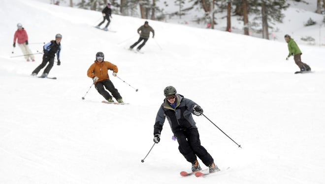 Skiers turn on the fresh snow during the first day of skiing at Loveland Ski Area in Georgetown, Colorado, in 2010.