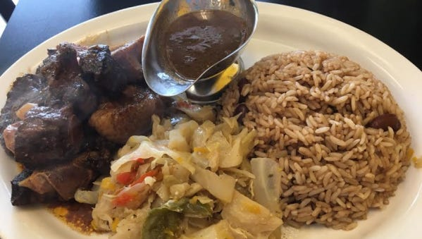One Love's oxtails were tender beef tails covered in rich brown gravy, a side of stewed cabbage along with rice and peas. Extra sauce was provided giving additional flavor.