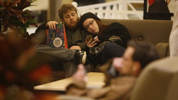 Aaron Bridge and Emily Goldsmith take a break from shopping at a local mall. The two have been shopping since about 1 a.m.