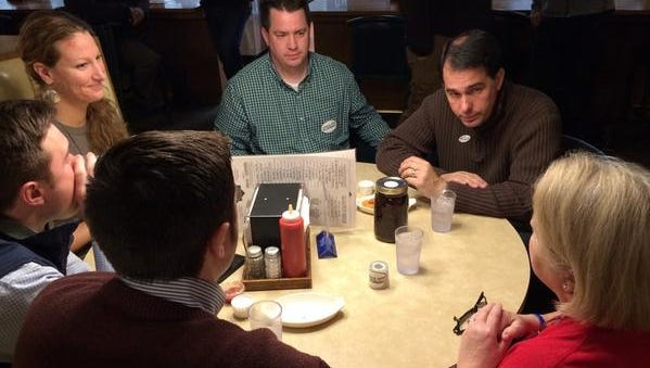 Wisconsin Gov. Scott Walker, upper right, listens during a campaign stop at Kroll's West in Ashwaubenon on Tuesday morning.