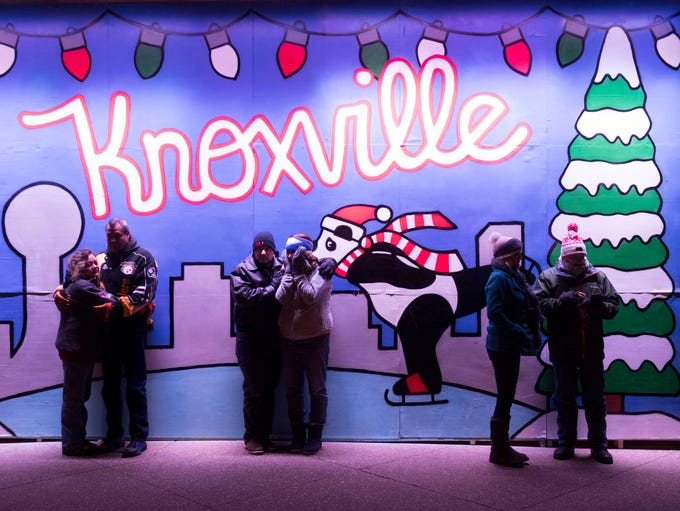 Couples gather near a mural on painted on the Holidays