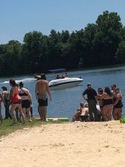 A crowd of people surrounds an 18-year-old woman who was injured in a jet ski accident at Cheatham Lake on Sunday, July 29.