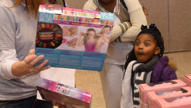 Zuri Smith reacts upon seeing the Electric Nail Art kit held by Rotarian Marilyn Carlin while trying to choose a gift with at the Doll & Toy Fund Distribution held Saturday at Alexandria Convention Hall. Zuri was with her mother Claudia Smith. The Doll & Toy Fund is sponsored by The Town Talk and the Rotary Club of Alexandria.