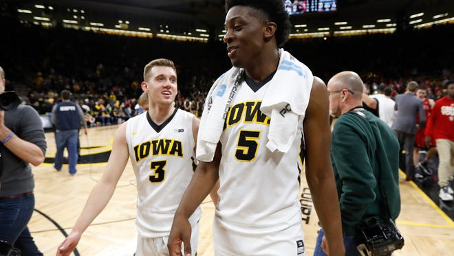 Iowa forward Tyler Cook (5) walks off the court with teammate Jordan Bohannon (3) after a first-round game in the NIT college basketball tournament, Wednesday, March 15, 2017, in Iowa City, Iowa. Iowa won 87-75.