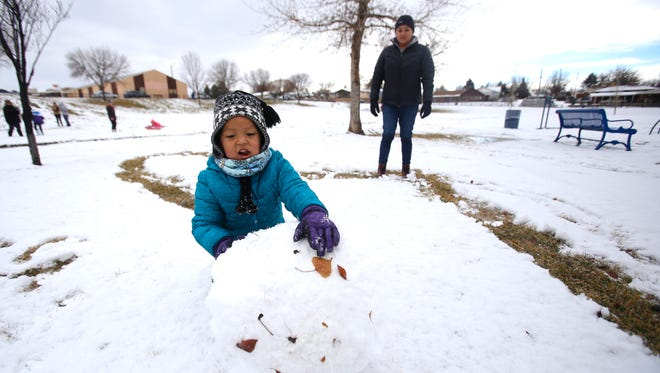 Scarlett Henderson, left,  and her mother, Nicole Henderson, prepare to build a snowman on Thursday at Brookside Park in Farmington. Schools in Aztec, Bloomfield and Farmington canceled classes on Thursday.