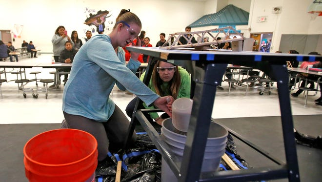 Lacy Fitzgerald, right keeps an eye on eighth-grader Emma Raye Gilmore's bridge after she successfully loaded 15 kilos of sand on it Saturday during a bridge-building competition at the 2016 Northwest Regional Science Olympiad at Mesa View Middle School in Farmington.