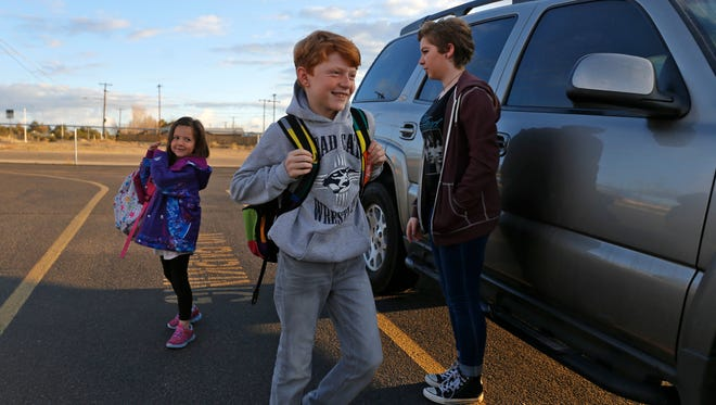 Delaney Howlett, left, and her brother Tylan Lovato are watched by their sister Ashleigh Lovato March 1 as they are dropped off at Country Club Elementary School in Farmington.