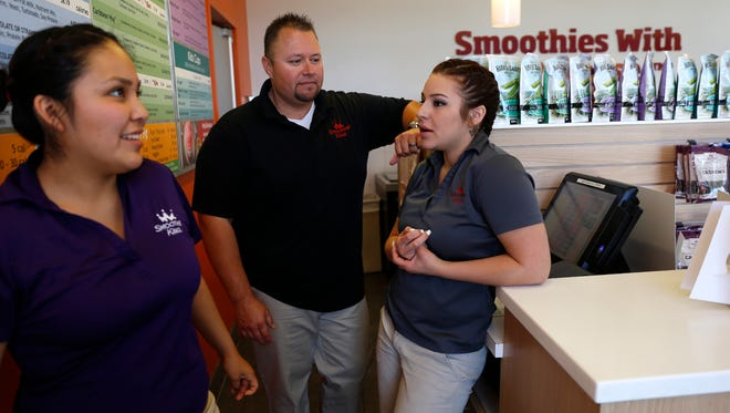 Smoothie King franchise owner Jason Simpson talks to his shift leaders Kody Begay, left, and Ciara Romero Tuesday at his store in Farmington.