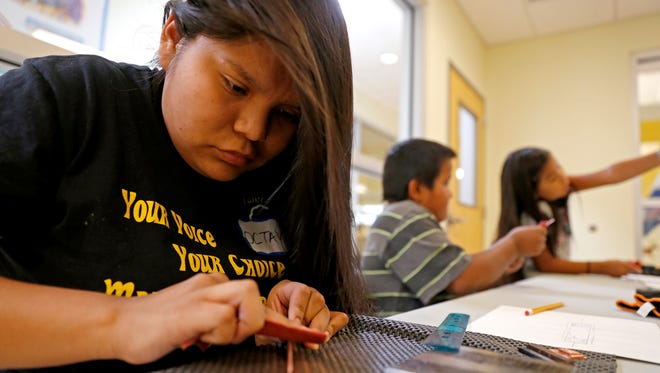 "Octavia Joe makes a bracelet during a session of last year's ""Dahayóígíí: A Cultural Youth Art Event"" on July 8 at the Shiprock Youth Complex."