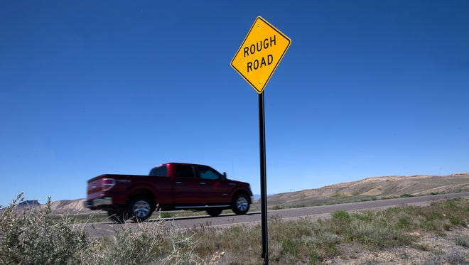 A vehicle passes a warning sign Friday near mile post 13 on Navajo Route 36 near the San Juan Chapter.