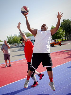 Las Cruces Sun-News Account Executive DaMarrio Mitchell powers past Classic Hits 98.7's DJ Adrian Cisneros during the Gus Macker Tournament at Field of Dreams, May 27, 2016. The Sun-News team, the Headliners, beat Adams Radio Group's Radioactive 21-8 in the annual Friday evening media game.