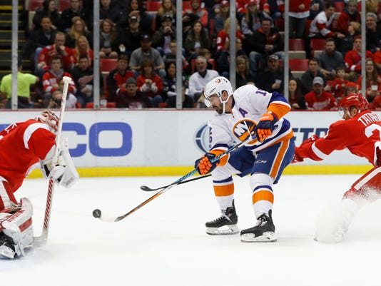 Detroit Red Wings goalie Petr Mrazek (34) blocks a shot by New York Islanders right wing Cal Clutterbuck (15) as Tomas Tatar (21) defends during the first period of an NHL hockey game Friday, Feb. 3, 2017, in Detroit. (AP Photo/Paul Sancya)