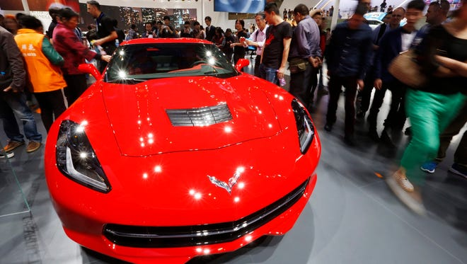 Visitors look at a car on display at the Chevrolet booth at the 16th Shanghai International Automobile Industry Exhibition in Shanghai