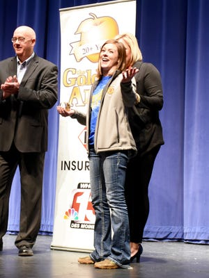 Grinnell High School's Ashley Wolfe, agriculture teacher and FFA adviser, receives the Golden Apple Award at a Pride Assembly at the school, presented by WHO-TV out of Des Moines.