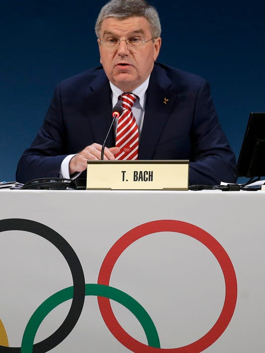 IOC President Thomas Bach delivers a speech at the start of the 127 th International Olympic Committee session in Monaco, Monday, Dec. 8, 2014. The IOC has approved plans for a more flexible sports program, a move that could lead to the inclusion of baseball and softball at the 2020 Tokyo Olympics.  The International Olympic Committee voted in favor of the revised system on the opening morning of a special two-day session to adopt President Thomas Bach's 40-point ``Olympic Agenda 2020'' reform package.  (AP Photo/Lionel Cironneau)