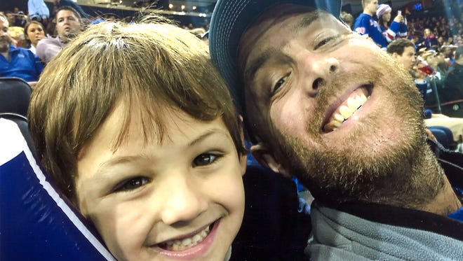Jay Heverly grabs a snapshot with his son Jeremiah at a sporting event.