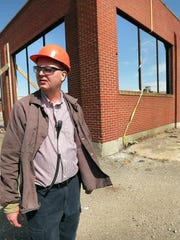 Plant engineer John Kelley stands in front of the preserved brick wall that will be the entrance of the new facility.