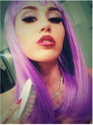 Miley dressed as 'Lil Kim for Halloween, complete with purple wig.
