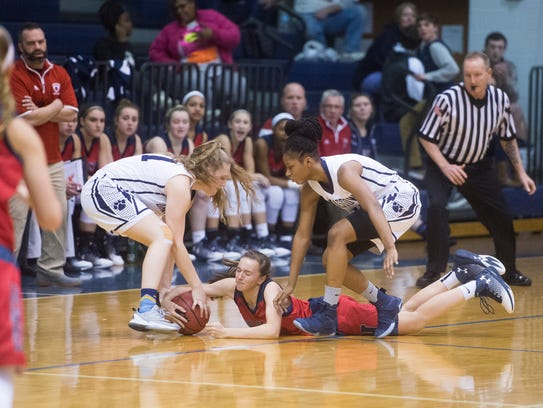New Oxford's Daelyn Stabler, center, fights for the