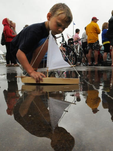 Owen Kreutzberg of Krakow finds a puddle to test his newly constructed sailboat he made while attending Marina Fest on Saturday in Sister Bay hosted by the Sister Bay Marina. The Festival also carried live music, food and refreshments, breakfast fund raiser, used book sale, children's games Waterboard Warriors water ski show and fireworks at dusk. Some of the photos appeared in Sept. 3 issue of Your Key to the Door Weekly inside the Door County Advocate. Tina M. Gohr/Your Key to the Door Weekly