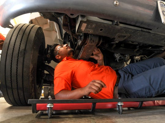 Luis Velazquez of Oxnard, a student in the Ventura College diesel mechanics program, looks under a truck to find a leak as he trains in Oxnard.