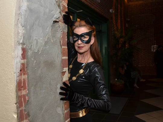 """Costumed as Catwoman, LaVonne French mans the door at Pensacon's inaugural """"Dress Up or Dress Up Costume Ball"""" at Pensacola Little Theatre."""