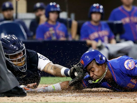 New York Mets' Yoenis Cespedes scores from third after hitting an RBI triple as San Diego Padres catcher Hector Sanchez is late with the tag during the seventh inning of a baseball game Tuesday, July 25, 2017, in San Diego. San Diego Padres first baseman Wil Myers picked up a throwing error on the play.