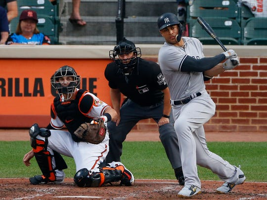 Jul 11, 2018; Baltimore, MD, USA;  New York Yankees right fielder Giancarlo Stanton (27) hits a rbi single scoring  designated hitter Aaron Judge (not pictured) during the third inning against the Baltimore Orioles at Oriole Park at Camden Yards.