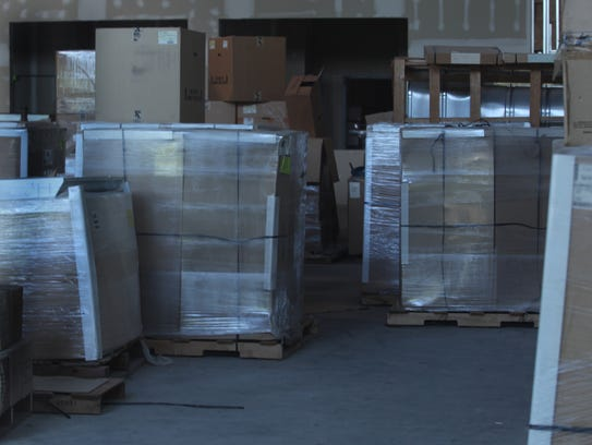 Supplies sit in boxes, some shrink-wrapped and on pallets