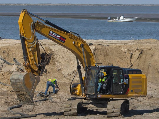 Construction workers move dirt behind an earthen dam at Rollover Pass on the Bolivar Peninsula on Jan. 21 in Gilchrist, Texas. The pass, once a popular fishing spot, is being filled in.