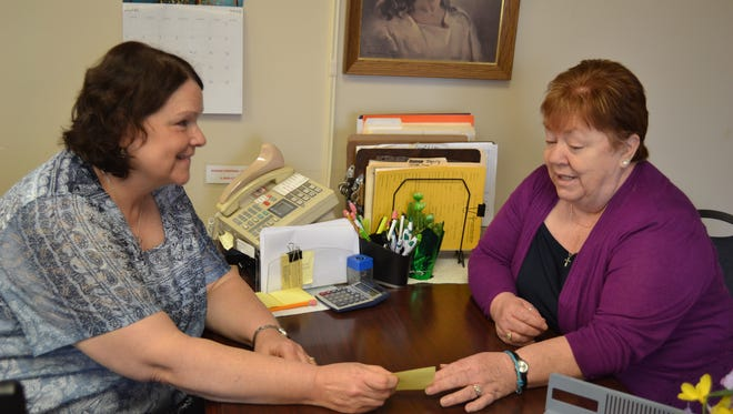 Office coordinator Vickie Bigler and Licensed Independent Chemical Dependency Counselor Tammy Broshious talk over office matters at Bigler's desk in the Fremont office of Lutheran Social Services.