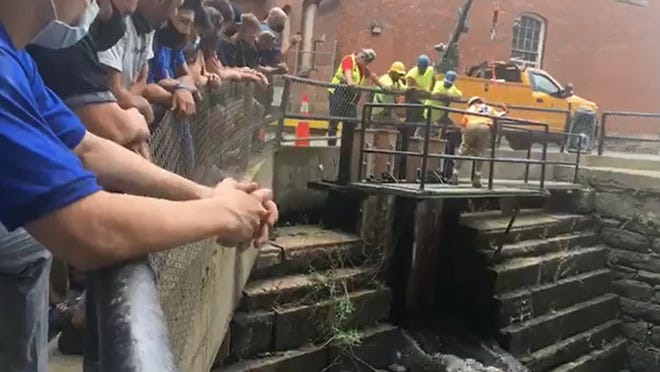 Diman students watch as water flows through new sluice gates that they created and were installed Friday by city work crews where the Quequechan River spills out after traveling under the city from South Watuppa Pond.