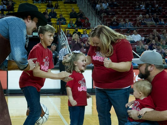 Aggie mascot Pistol Pete, left, Ethan Maki, 13; Kayla Maki, 5; Ashley Maki, mother of the children shown; Brian Maki, father, and Carer Maki, 1, all react to news that the family will be given a free trip to Disney World by the Make-A-Wish New Mexico organiztion.