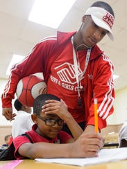 Gary Williams helping Zavier Simon with homework at
