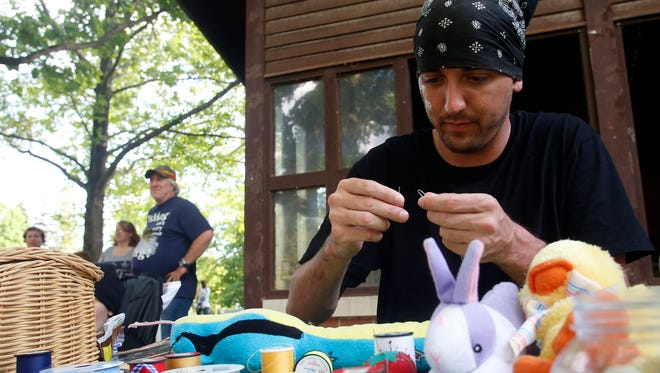 John Baker mends a plush snake during the Teddy Bear Picnic at Crapo Park Sunday, June 1, 2014, in Burlington, Iowa. The event was put on by the Alcohol and Drug Dependency Services and the City of Burlington.  (AP Photo/The Hawk Eye, Rachel Jessen)