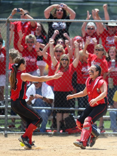 Battery-mates Regan Green (left) and Sara Jo Whaley start the celebration after Green threw a complete game, 3-0 win against Caravel in the final of the DIAA state high school tournament, Saturday, May 31, 2014 at Polytech High School. Green took a perfect game into the final inning.