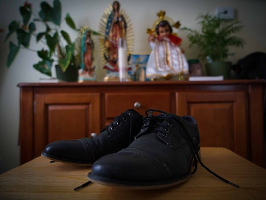 The shoes of Jose Santillan, who was taken into custody by ICE, rest near a religious altar at his home in Wilmington.