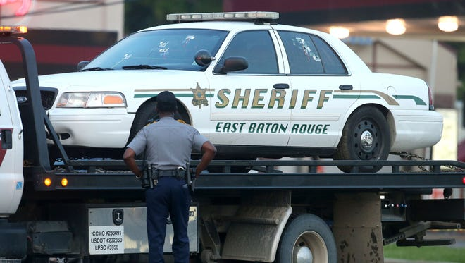 A police officer stands in front of an East Baton Rouge police car with bullet holes as it's hauled away from the scene where three police officers were killed.
