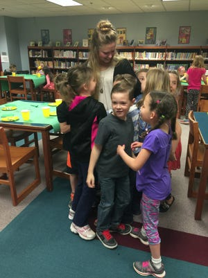 Shelby Douglas gets a hug-attack from her first graders at Northwest Elementary School during a surprise party they put on for her.