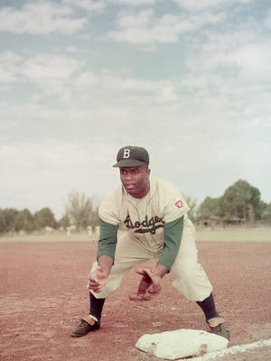 American professional baseball player Jackie Robinson (1919-1972) of the Brooklyn Dodgers, dressed in a road uniform, crouches by the base and prepares to catch a ball, 1951. Throughout the course of his baseball career Robinson played several positions on the infield as well as serving as outfielder.