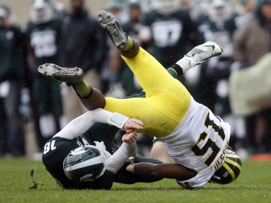 MSU's Connor Cook tackled by U-M linebacker James Ross III in 2014.